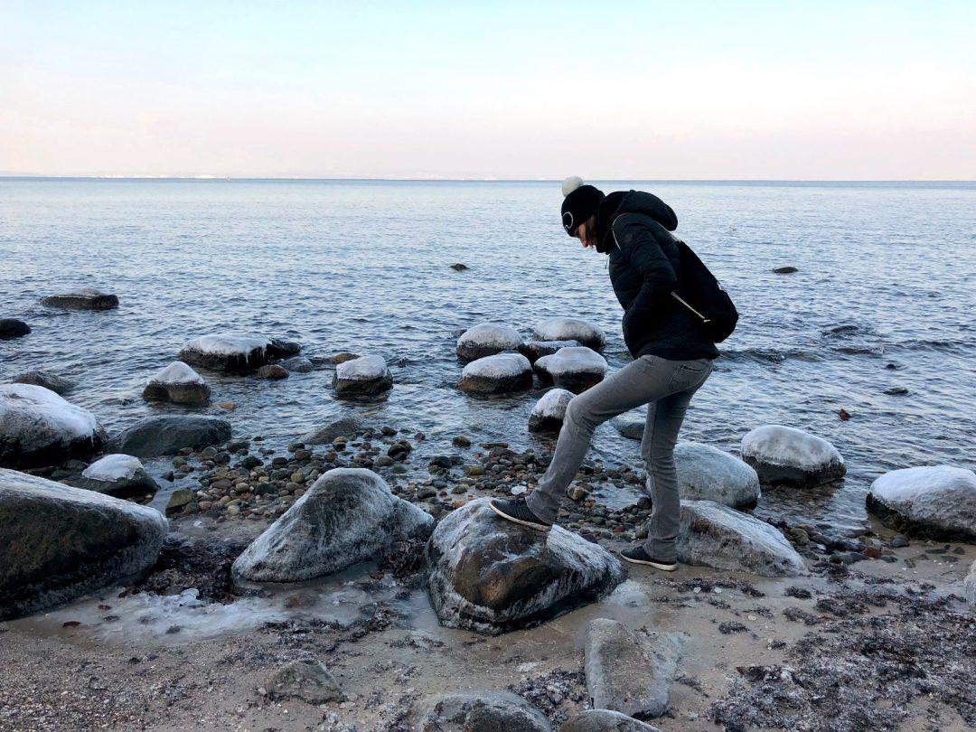 Frau am steinigen Strand